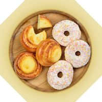 Wooden dish of cheese pies and donuts.
