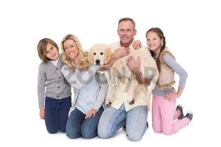 Family with their dog posing and smiling at camera together