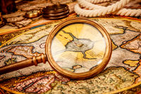 Vintage magnifying glass lies on the ancient map of the North Pole (also Hyperborea).