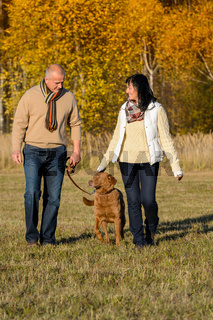 Couple walking dog in autumn sunny park