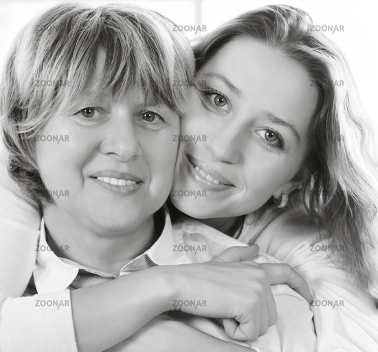 Black and white close up portrait of a mature mother and adult daughter being close and hugging