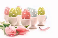 Colorful spotted Easter eggs in white cups