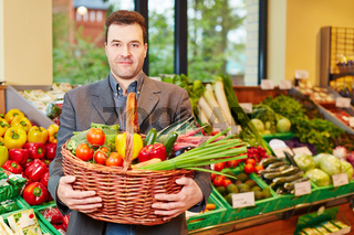 Mann trägt Korb mit Gemüse im Supermarkt