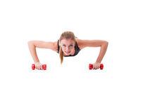 Smiling female athlete push-ups on dumbbells