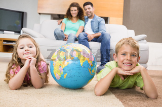 Smiling siblings lying on the rug with a globe