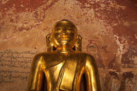 Ancient architecture of old Buddhist Temples at Bagan Kingdom, Myanmar (Burma). Golden Buddha statue inside one of pagoda ruins