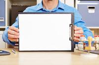 Mann hält Blatt Papier auf Klemmbrett