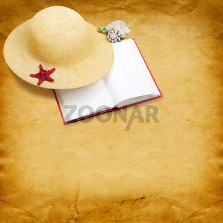 Straw hat with book and red starfish on shabby paper background