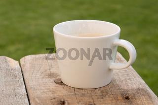Kaffeebcher auf einem Holzbrett