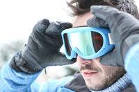 Mann im Skiurlaub setzt Skibrille auf