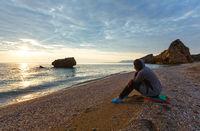Woman on Potistika beach. Sunrise view (Greece)