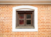 Small wooden window and brick wall