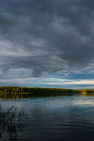 Sunset over the forest lake with dramatic sky.