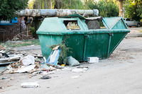 Overfilled trash dumpster in ghetto neigborhood outdoors