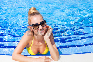 Gorgeous blonde woman in a yellow bikini in the water