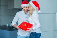 Young woman kissing her husband at Christmas