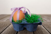 Egg in a easter nest on a table.