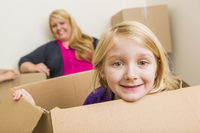 Young Mother and Daughter Having Fun With Moving Boxes