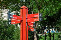 Multiple way red signpost in city park