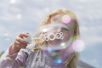 A little girl blowing soap bubbles in the air