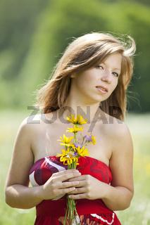 Vertraeumtes Maedchen mit Blumen in der Hand