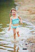 Lachendes Mädchen rennt durch Wasser