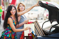 Two women with shopping bags at the car