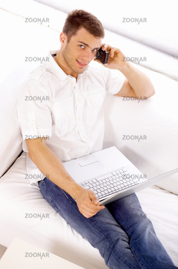 Young Salesman on Couch Using Phone and Laptop