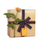 Beautiful gift box in gold paper with bow and rose isolated on a white background