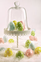 Cake stand with easter eggs and white feathers