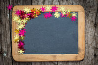 Christmas frame of confetti on blackboard