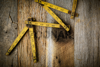 Old Tape Measure on Rustic Wood Background