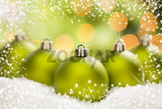 Green Christmas Ornaments on Snow Over an Abstract Background