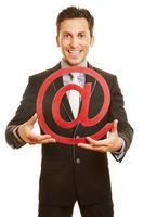 Geschäftsmann hält at-Zeichen als Symbol für Internet