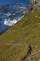 Hiker on a hiking trail in the Swiss Alps