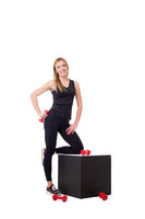 Smiling female athlete posing with dumbbells