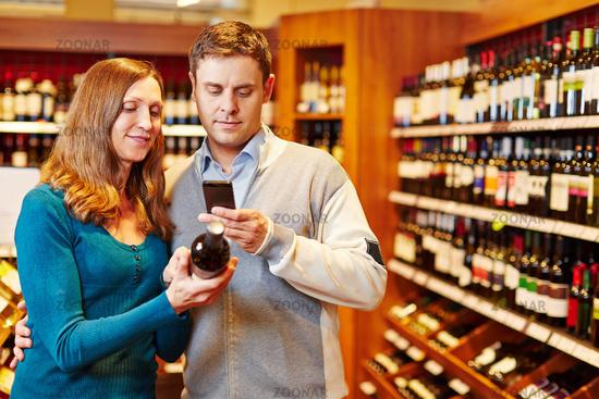 Mann fotografiert Wein im Supermarkt