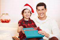 Vater und Sohn mit Geschenk an Weihnachten
