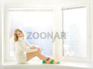 Beautiful girl sitting at the window