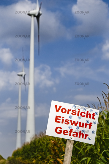 Danger sign in front of wind turbines