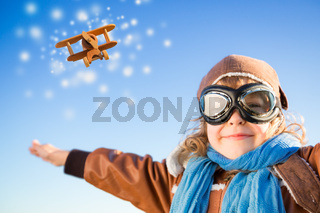 Happy kid playing with toy airplane in winter