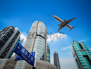 upward view airplane with modern building