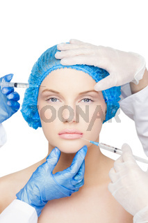 Surgeons making injection on pretty blonde