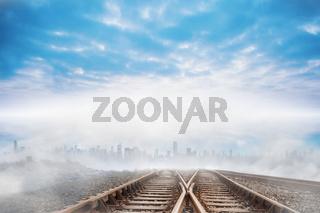 Train tracks leading to city on the horizon