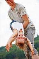 Vater läßt Tochter auf dem Arm fliegen