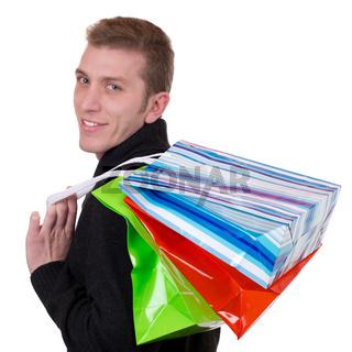 Lachender junger Mann beim Einkaufen mit Taschen