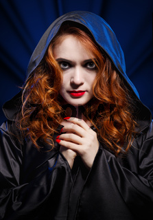 Young witch on blue light background