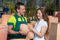 Employee in garden center selling pottery to customer