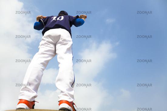 baseball player holding a bat with cloud backgroun