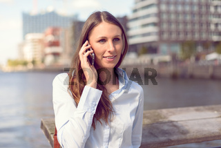 Attraktive junge Frau telefoniert mit ihrem Handy